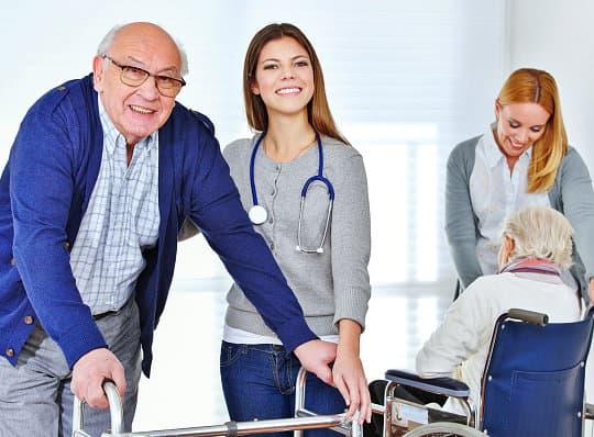 nurse assisting the senior man on the walker