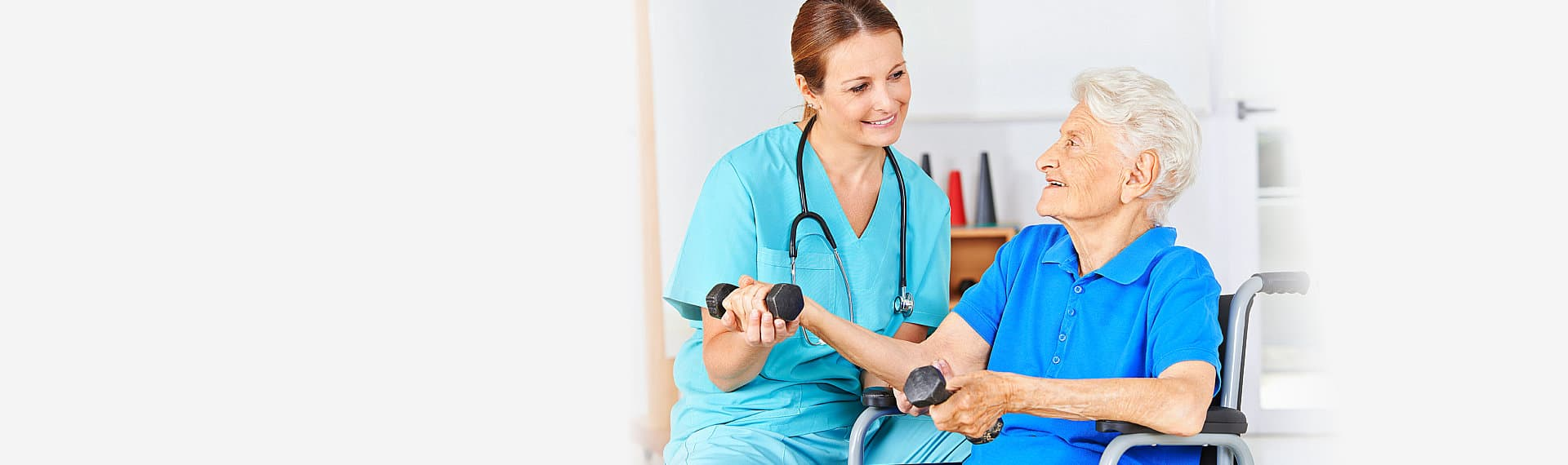 nurse assisting the senior woman on wheelchair to carry the dumbbell