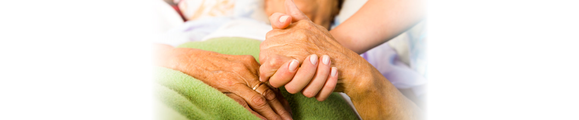 hands of a senior woman held tight by a caregiver